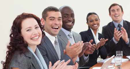 Happy businessteam clapping in a meeting